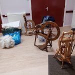A selection of small spinning wheels with raw wool.